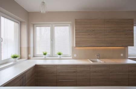 Simple modern spacious kitchen with wooden furniture Foto de archivo