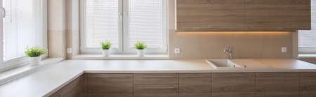 puertas de madera: Cocina bien iluminada con una gran encimera y puertas de armarios de madera Foto de archivo