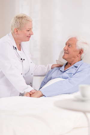 nursing treatment: Photo of mature nurse taking care about old patient Stock Photo