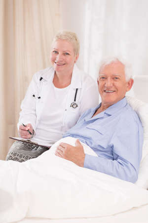 man doctor: Photo of mature caring doctor and her elderly patient Stock Photo