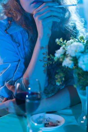 drinking problem: Seductive woman smoking a cigarette and drinking wine Stock Photo