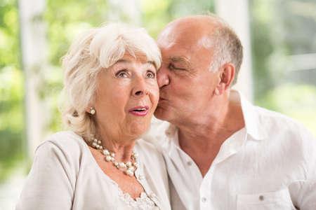 sorpresa: Senior marido besando a su esposa en la mejilla