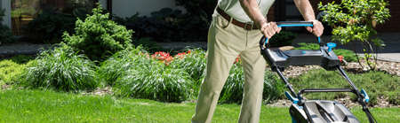 mow: Panorama of male horticulturist tending lawn in his backyard Stock Photo