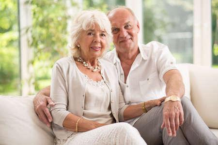jubilados: Pareja de ancianos amorosa sentado en el sofá Foto de archivo