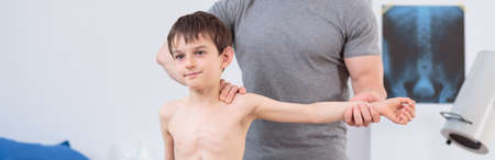 osteopath: Little child exercising with physical therapist - panorama Stock Photo