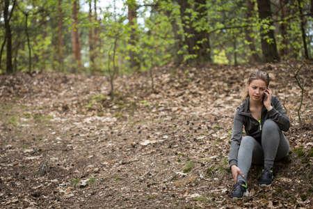 deportistas: Mujer que activa con llamar tobillo espolvoreado en busca de ayuda