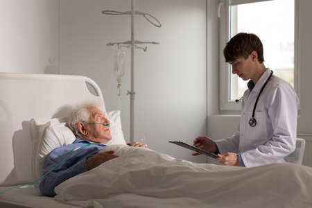 terminals: Young doctor talking with ill senior patient Stock Photo