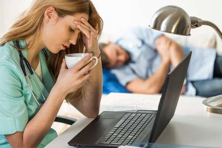 overworking: Female medic having headache and other doctor sleeping