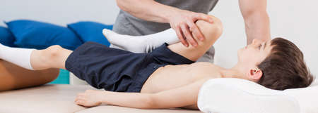 Close-up of physiotherapist stretching young patients leg