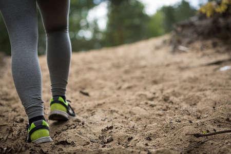 sandy feet: Close-up of running girls feet on sandy base Stock Photo