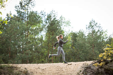 hillock: Active young girl running on sandy hillock