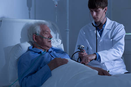 doctor examine: Young doctor measuring blood pressure in hospital