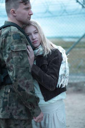 husband: Sad woman hugging military husband and saying goodbye