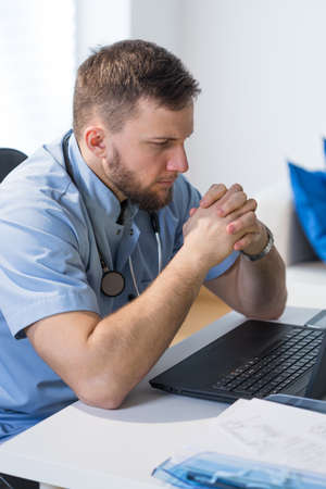 overworking: Tired young doctor working overtime at hospital Stock Photo
