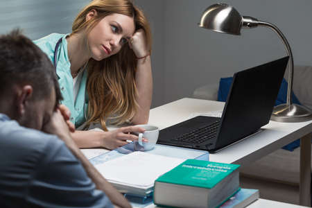 physician: Tired young medical staff sitting at the desk Stock Photo