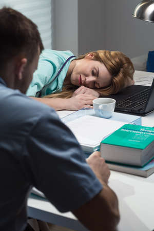 overworking: Young medical staff working overtime at hospital Stock Photo