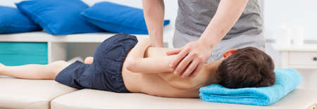 rehabilitation: Physiotherapist stretching body of little patient - panorama Stock Photo