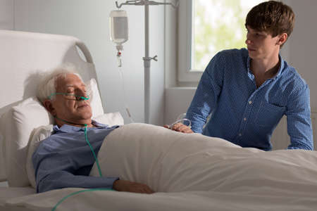 seriously: Terminally ill senior man staying in hospital Stock Photo