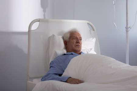 Sad elder man lying in hospital bed