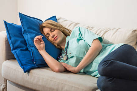 physician: Young female doctor sleeping during night shift Stock Photo