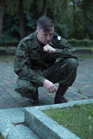 military cemetery: Image of young caucasian soldier visiting cemetery