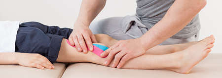 kneecap: Patient with kinesiology tapes on the knee Stock Photo