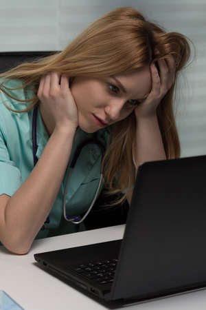 physician: Young female doctor using laptop at work Stock Photo