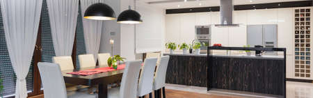 Panorama of modern kitchen with dining table Imagens