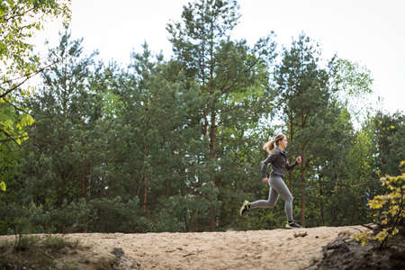 scarp: Woman jogging on sandy scarp in the forest Stock Photo