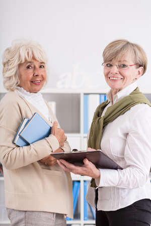 retirement community: Smiling mature women are talking about classes