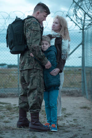 deployment: Family and soldier in military saying goodbye