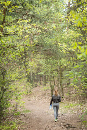 woman alone: Muscular young woman walking in the woods alone Stock Photo
