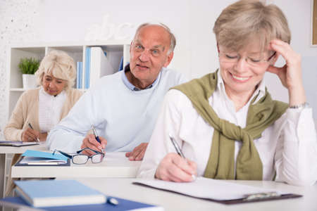 taking notes: Mature students are taking notes on the classes