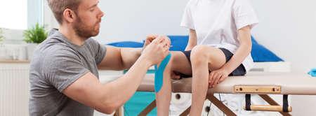 fisioterapia: Fisioterapeuta joven masculino para trabajar con el peque�o paciente