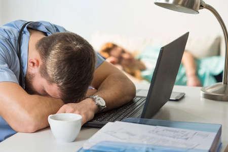 agotado: Doctor cansado con exceso de trabajo que duerme en el escritorio