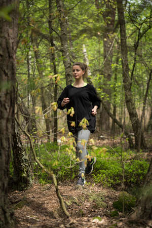 Athletic active girl and morning running in forest Stock Photo