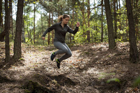 hillock: Athletic woman jumping through hillocks during jogging Stock Photo