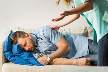 overworking: Tired doctor sleeping on the couch in hospital Stock Photo