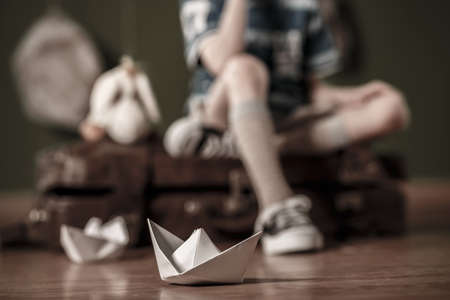 daydreamer: Paper boat lying on the wooden floor