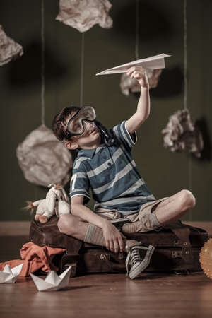 boys toys: Sitting on suitcase and playing with paper plane