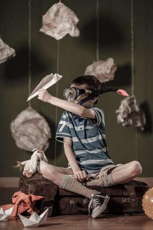 ni�os jugando: Muchacho con la m�scara de snorkel y avi�n de papel Foto de archivo