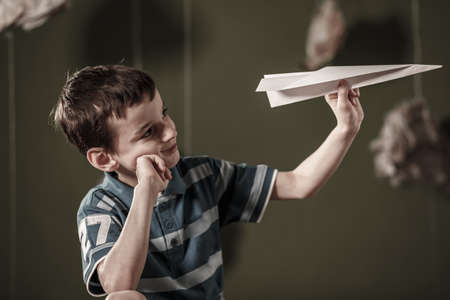 Image of cute boy holding paper airplane