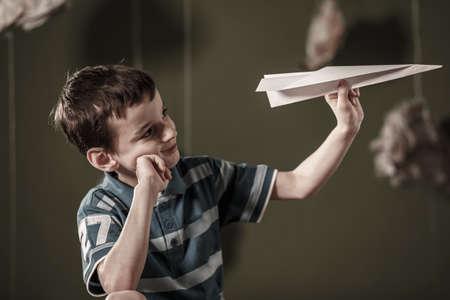 Imagen de lindo niño de la celebración de avión de papel Foto de archivo - 43445143