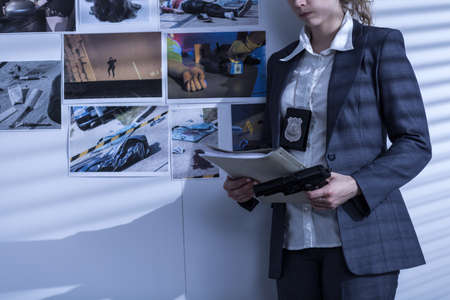 femme policier: Photo de la policière avec badge et arme présenter des preuves du crime