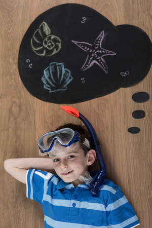 ocean floor: Boy with mask and snorkel dreaming about diving Stock Photo