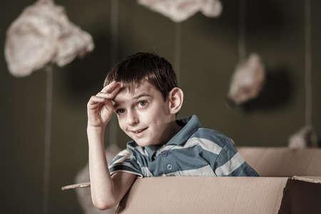 boite carton: Heureux petit garçon jouant dans la boîte de carton