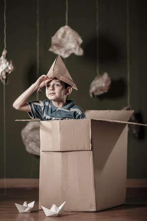 Muchacho con el sombrero de papel que juega en caja de cartón