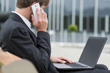 persona llamando: El hombre de negocios está hablando por el teléfono y el trabajo con el ordenador portátil