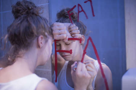 Picture of bulimic girl and red writing fat on mirror Imagens - 43644313