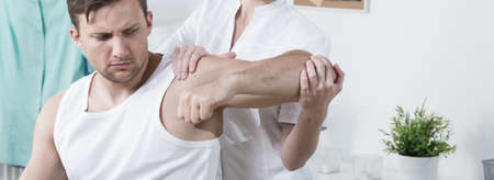 rehabilitated: Young man is rehabilitated by female physiotherapist Stock Photo
